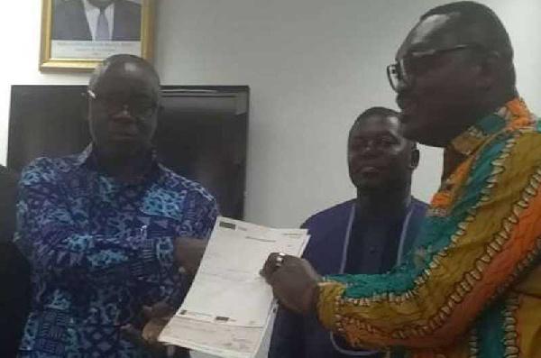 Okatakyie Amankwaa Afrifa presenting the cheque to Lands Minister Kwaku Asomah-Cheremeh